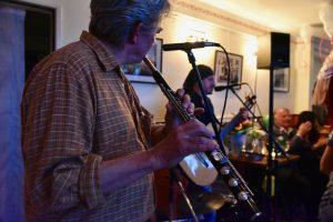Querflötenspieler im Vordergrund mit dem Rest der Band im Hintergrund